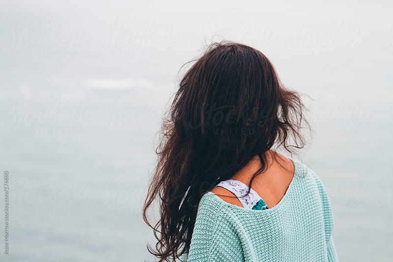 young woman looks out at the ocean by Jesse Morrow for Stocksy United