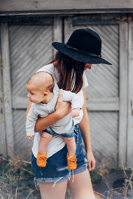 Mother casually holding her baby by Treasures & Travels for Stocksy United
