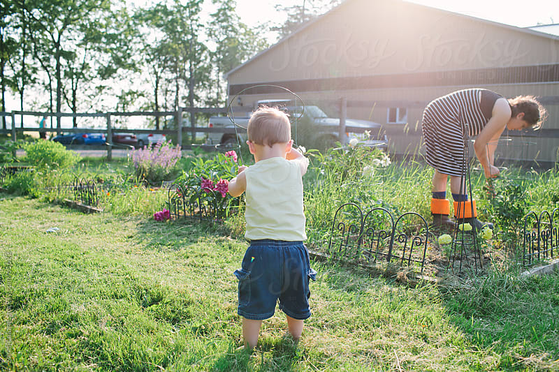 A little boy helping his mom garden. by Sarah Lalone for Stocksy United