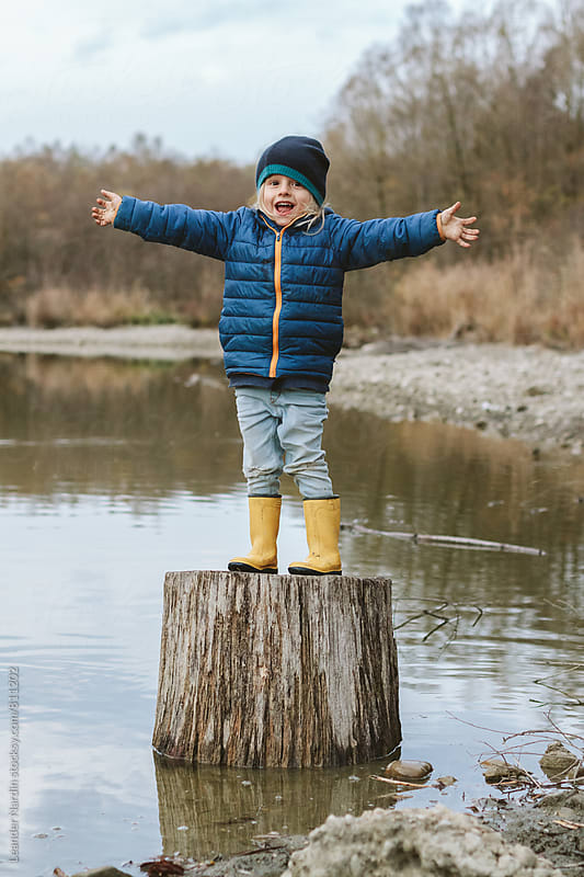 little boy standing on a trunk in a small lake by Leander Nardin for Stocksy United