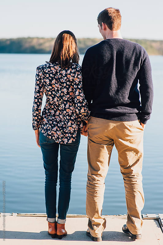 Couple at the End of a Boat Dock Looking at the Lake by michelle edmonds for Stocksy United