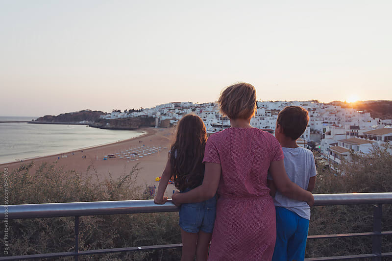 Family watching the sunset. by Dejan Ristovski for Stocksy United