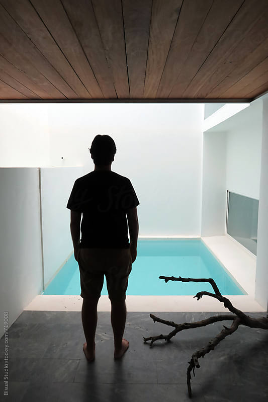 Man standing in an interior of a modern house with pool by Bisual Studio for Stocksy United