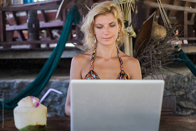 Woman Looking at Laptop in a Tropical Cafe by Mosuno for Stocksy United