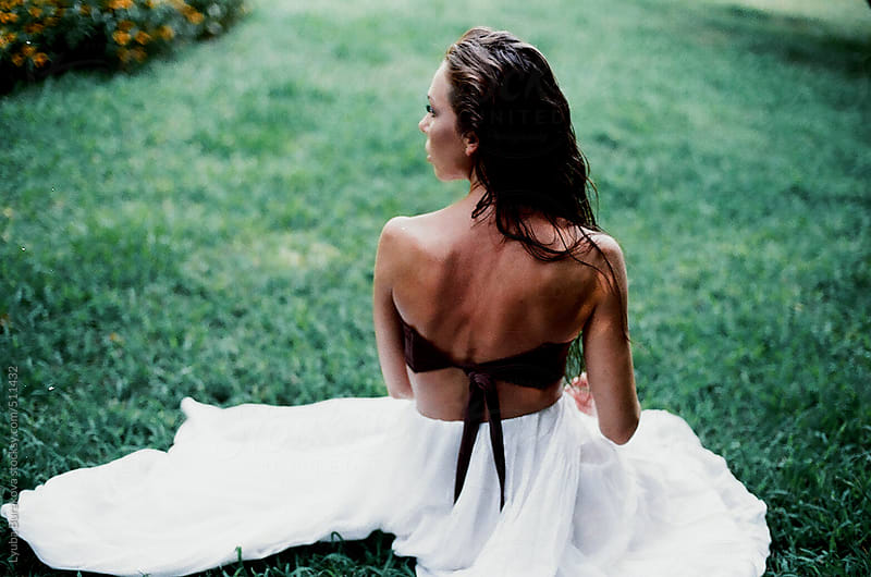 Back view of the woman sitting on grass by Lyuba Burakova for Stocksy United