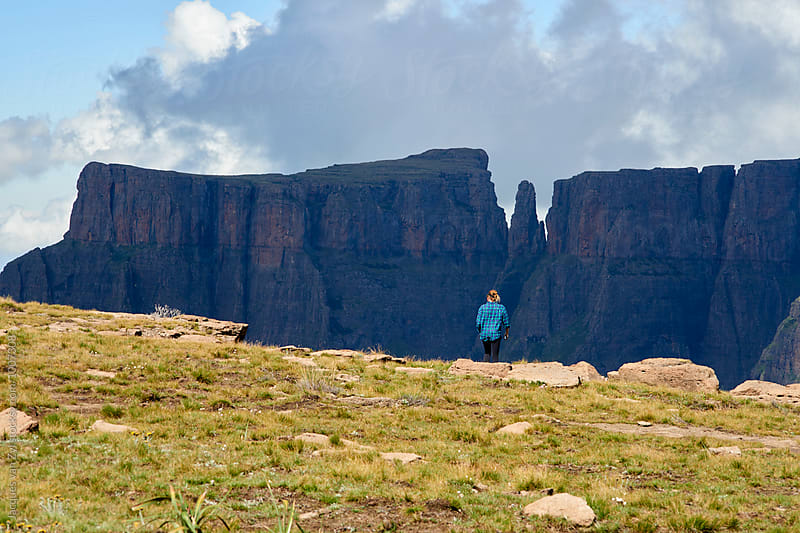 Young hiking woman admiring a speared mountain top. by Jacques van Zyl for Stocksy United