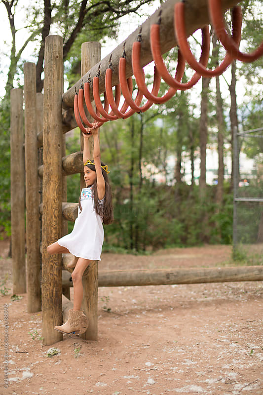 Young Girl Swinging on Monkey Bars by Gabrielle Lutze for Stocksy United