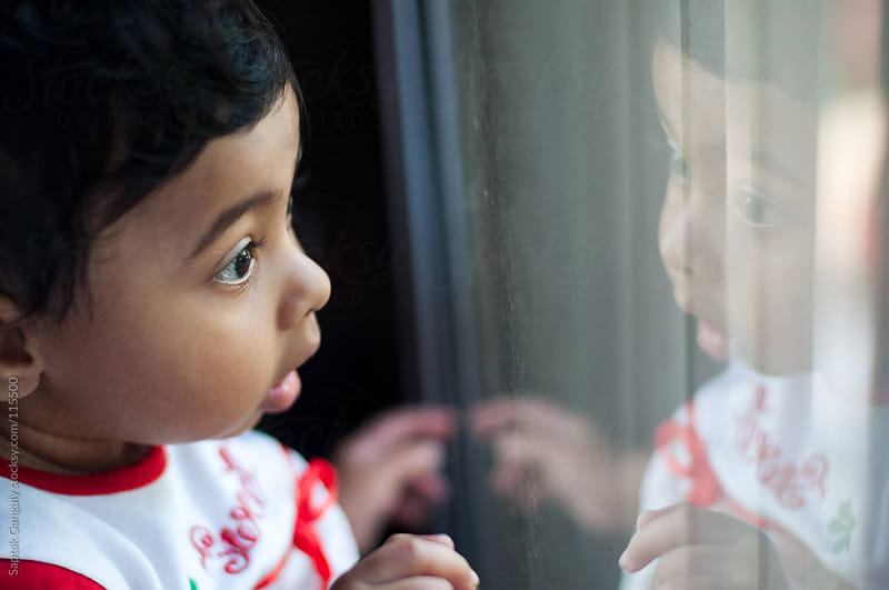 Baby girl looking amazed at her reflection on a window glass by Saptak Ganguly for Stocksy United