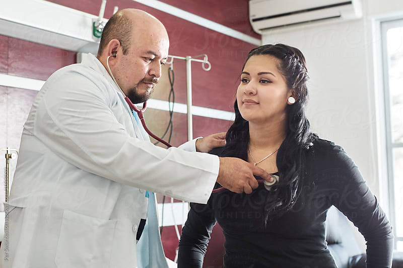 Doctor listens attentively to patient's heartbeat by Per Swantesson for Stocksy United