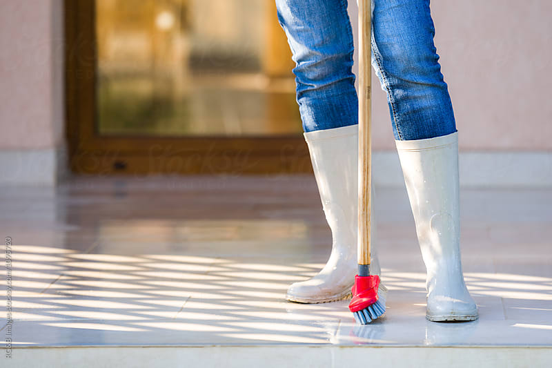 Woman in rubber boots scrubbing the terrace floor by RG&B Images for Stocksy United