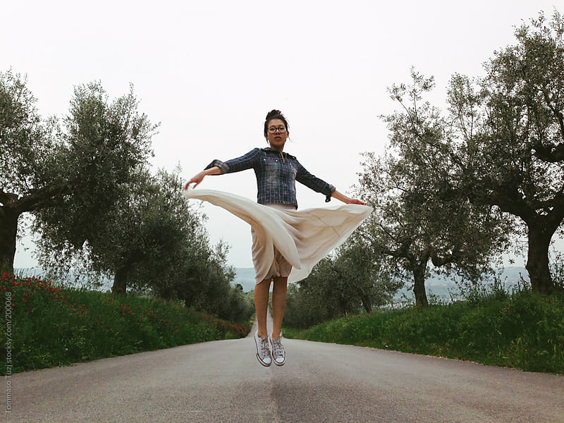 Girl jumping on the road by Tommaso Tuzj for Stocksy United