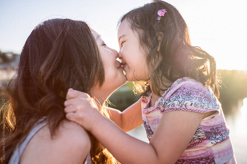 Happy Asian girl kissing her mother by Suprijono Suharjoto for Stocksy United