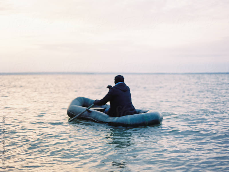 Man in row boat. Back view, film by Danil Nevsky for Stocksy United