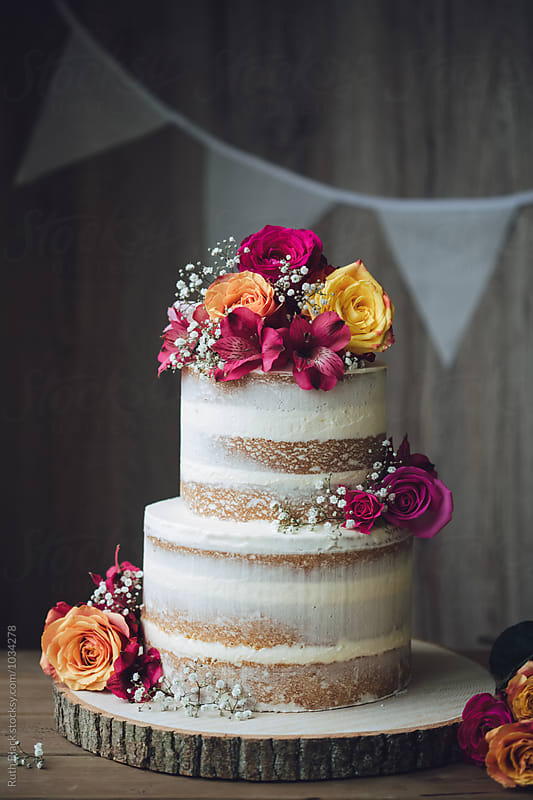 Wedding cake decorated with fresh flowers by Ruth Black for Stocksy United