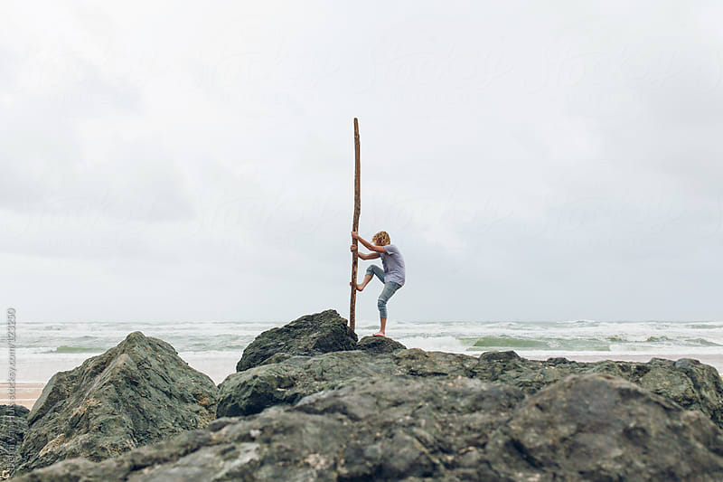 Wild marooned man standing on rocks holding a piece of driftwood. by Denni Van Huis for Stocksy United