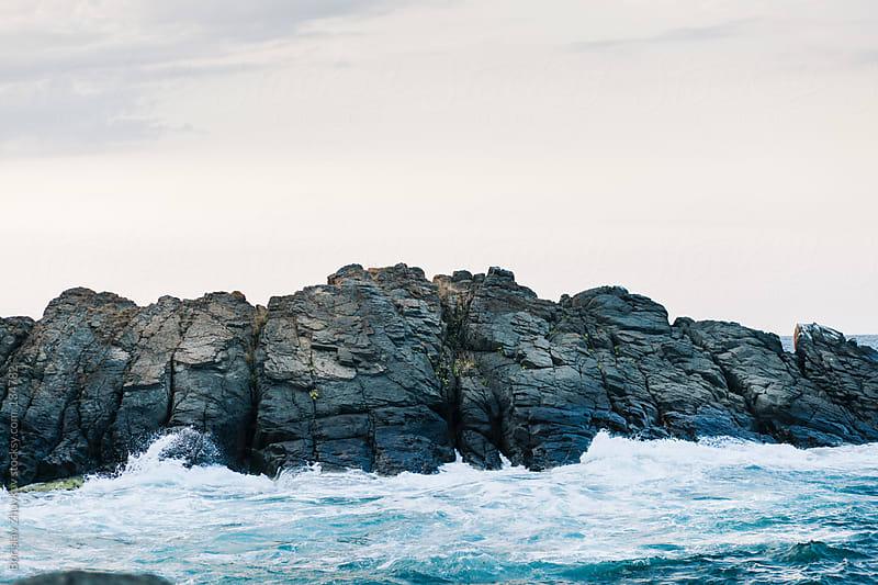 Sea water splashes on the rocks by Borislav Zhuykov for Stocksy United