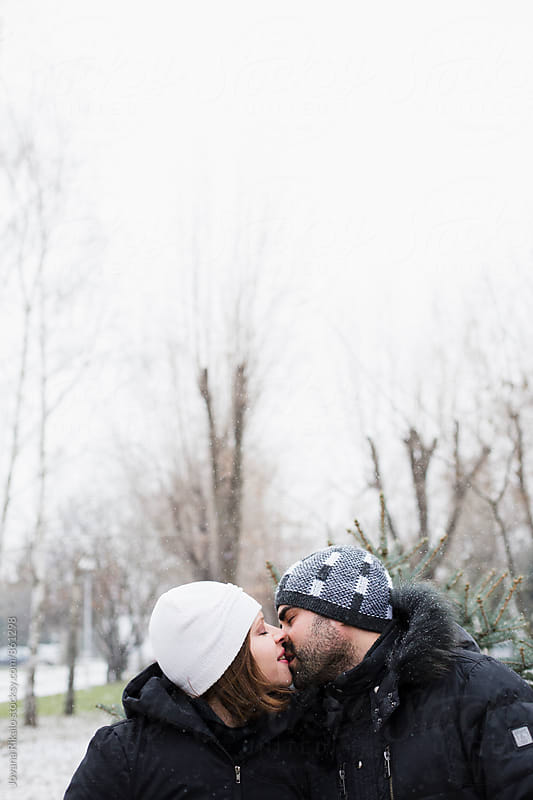 Couple is kissing on a snow by Jovana Rikalo for Stocksy United