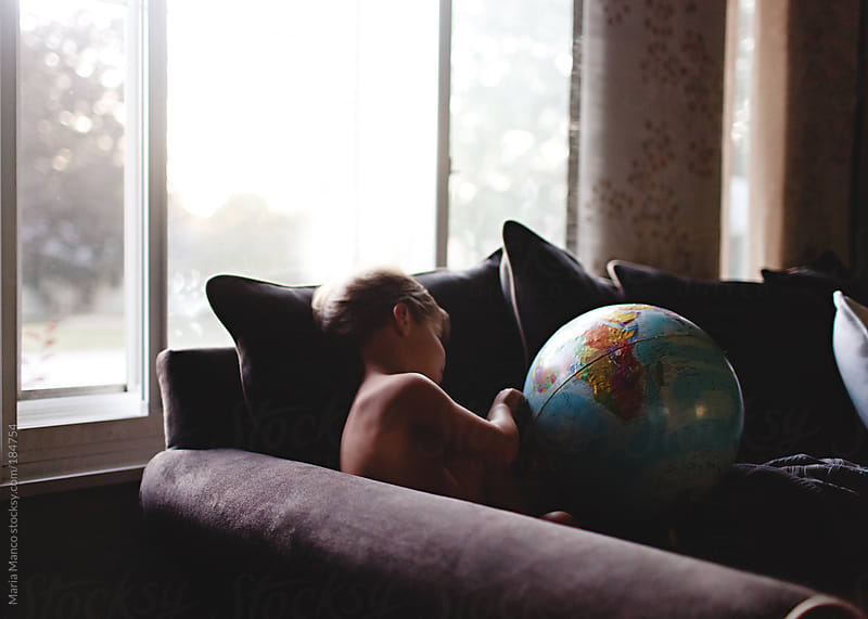 boy looks at globe on couch by Maria Manco for Stocksy United
