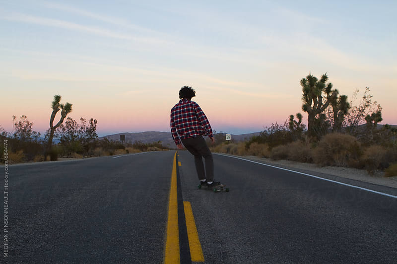 Man Skating on Road at Sunset by MEGHAN PINSONNEAULT for Stocksy United