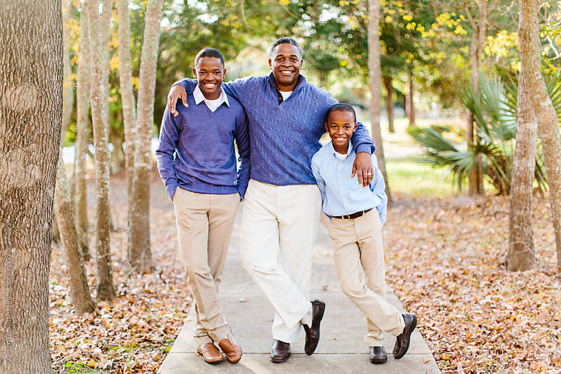 A father and his two young sons by Kristen Curette Hines for Stocksy United