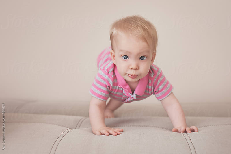Cute and lovely baby girl in a starting position by Lea Csontos for Stocksy United