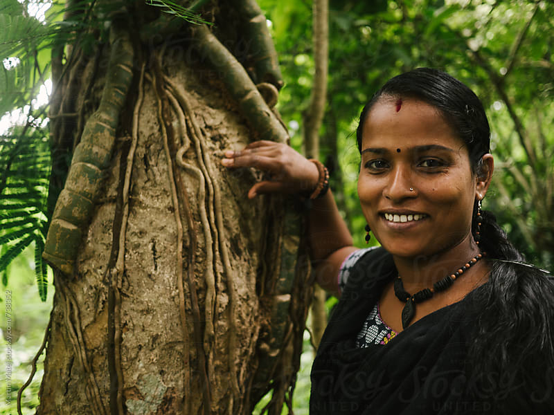 Happy Indian girl leaning towards tree in tropical forest by Martin Matej for Stocksy United
