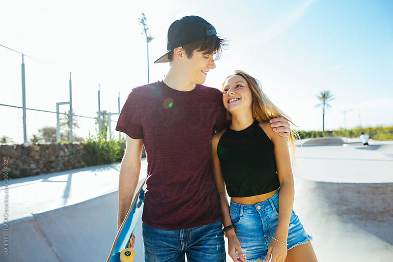 Teenage couple having fun in a skate park on a sunny summer day. by BONNINSTUDIO for Stocksy United