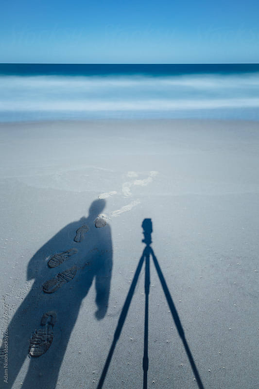 Shadow of a photographer on the beach, long exposure. by Adam Nixon for Stocksy United