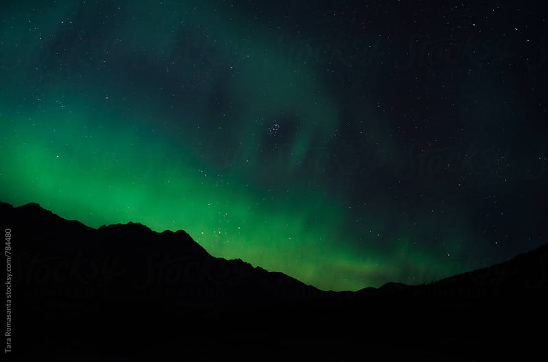 Northern Lights and stars over a mountain ridge by Tara Romasanta for Stocksy United
