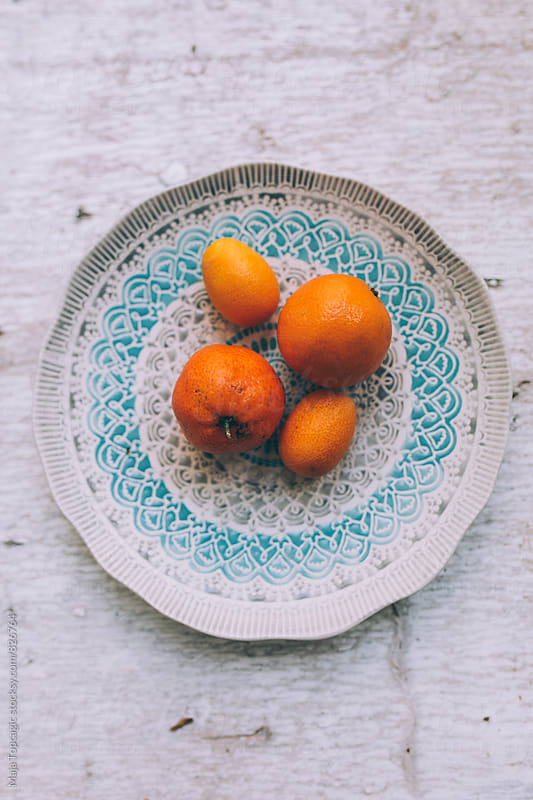 Clementines on a plate by Maja Topcagic for Stocksy United