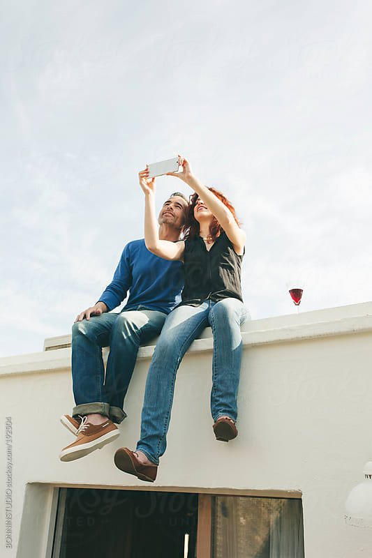 Beautiful couple taking a picture of themselves with smart phone on the rooftop. by BONNINSTUDIO for Stocksy United