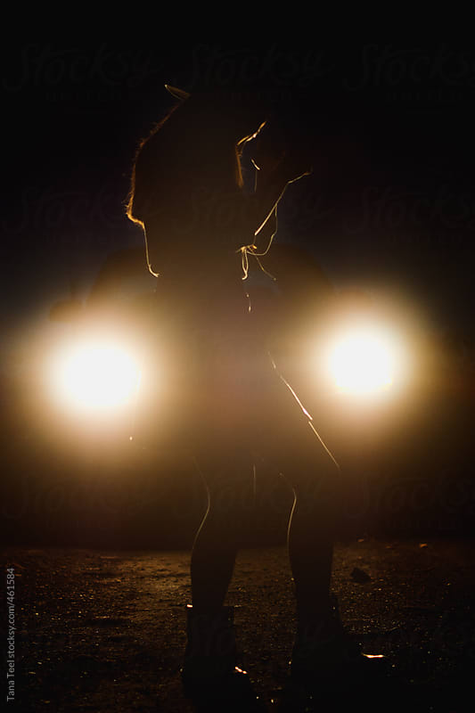 Silhouette of teenager dancing in front of car lights by Tana Teel for Stocksy United