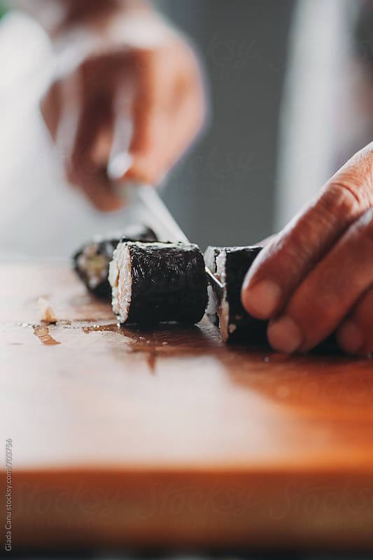 Cutting a sushi roll by Giada Canu for Stocksy United