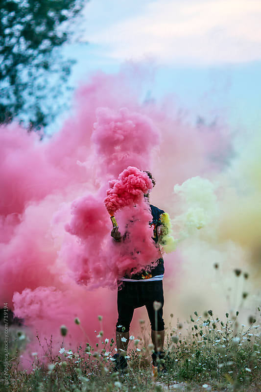faceless,fashionable hipster man holding colorful smoke bombs in  nature by Igor Madjinca for Stocksy United