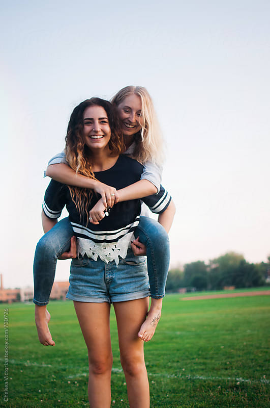 Sisters on a piggyback ride by Chelsea Victoria for Stocksy United