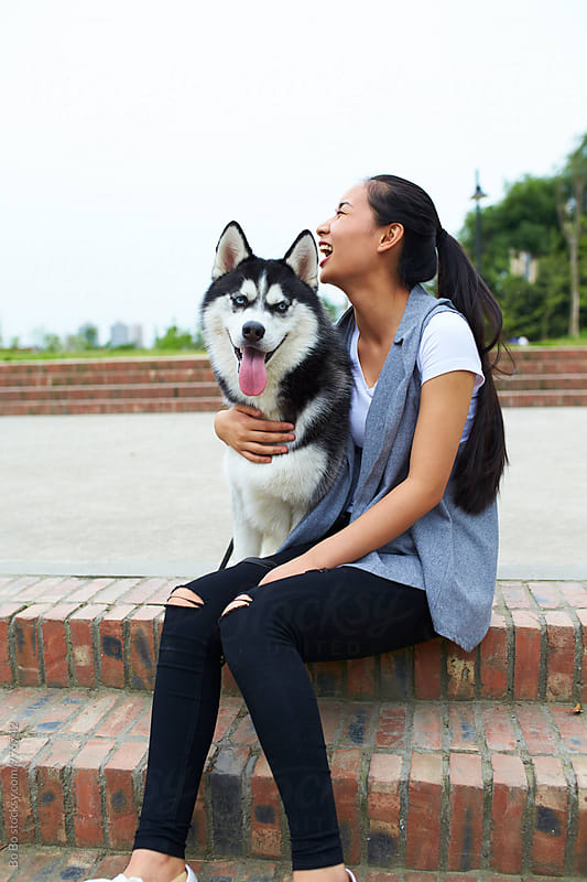 young asian woman with her husky dog outdoor by Bo Bo for Stocksy United
