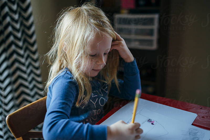 A Little Girl With Strawberry Blonde Hair Focuses on her drawing by Amanda Voelker for Stocksy United
