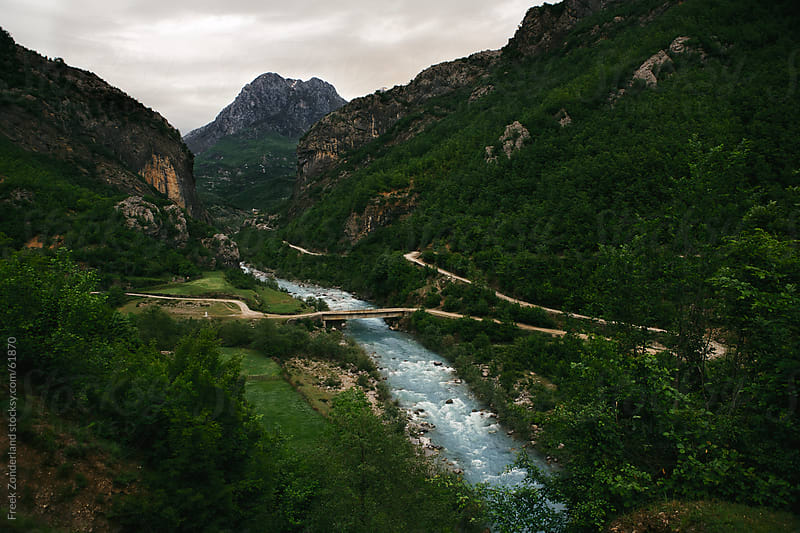 Bridge in a valley crossing a blue river by Freek Zonderland for Stocksy United
