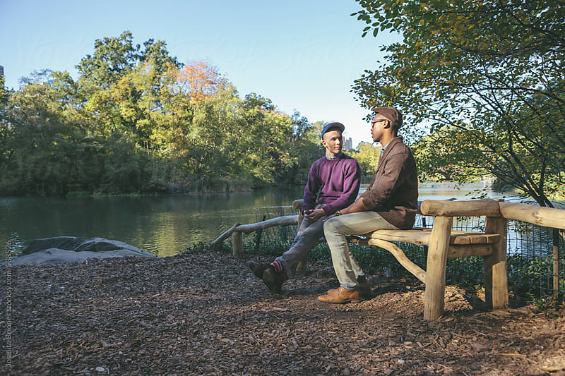 Young Gay Couple Talking and Sharing Intimate Moment Together in New York's Central Park by Joselito Briones for Stocksy United