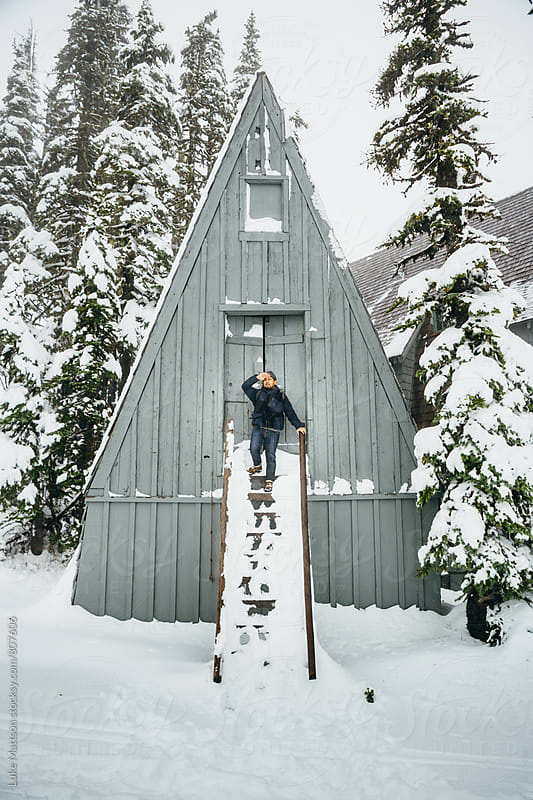 Man Standing On Steps Looking Out In Front Of Mountain Cabin In Snow by Luke Mattson for Stocksy United