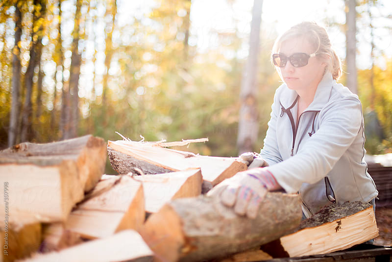 Woman Stacking Hardwood Firewood In Autumn Outdoors at Cottage by JP Danko for Stocksy United