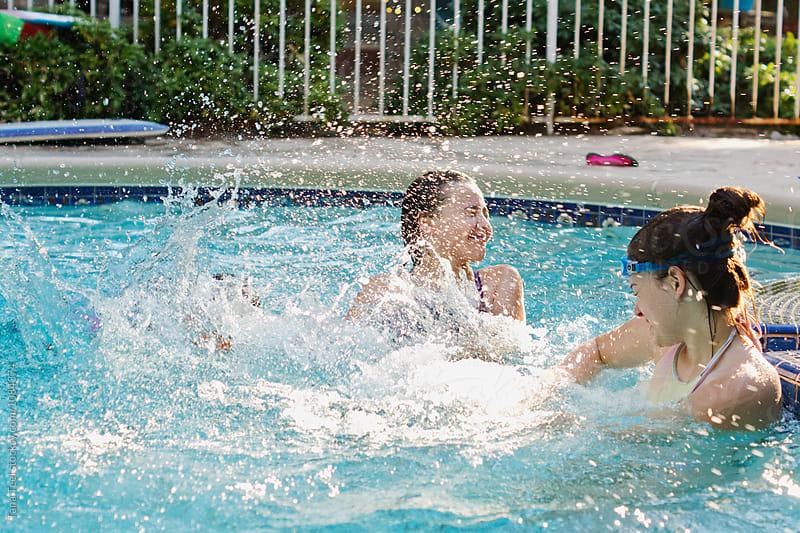 kids splashing in pool by Tana Teel for Stocksy United