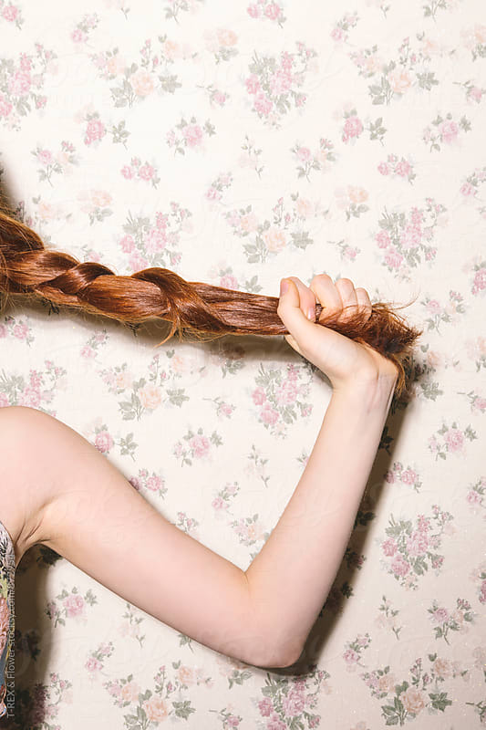 Ginger woman holding her braid by Danil Nevsky for Stocksy United