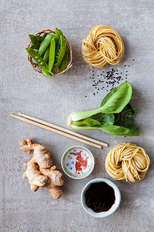 Snow peas, egg noodles, bok choy, ginger root, sesame seeds, soy sauce and chopsticks by Nadine Greeff for Stocksy United
