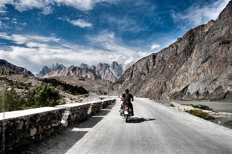 Motorcyclist rides his motorcycle on a mountain road towards the Karakorum highway by Jean-Claude Manfredi for Stocksy United