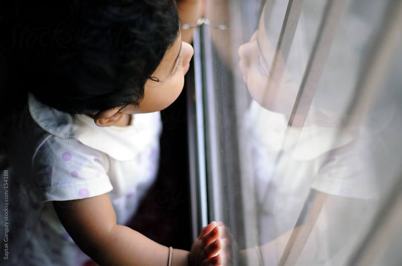 Baby girl looking out the window,top view by Saptak Ganguly for Stocksy United