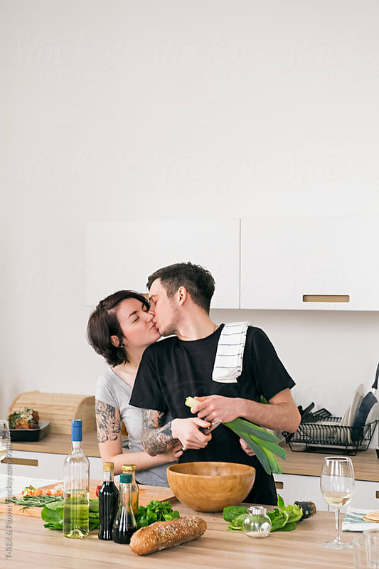 Couple kissing in the white kitchen by T-REX & Flower for Stocksy United