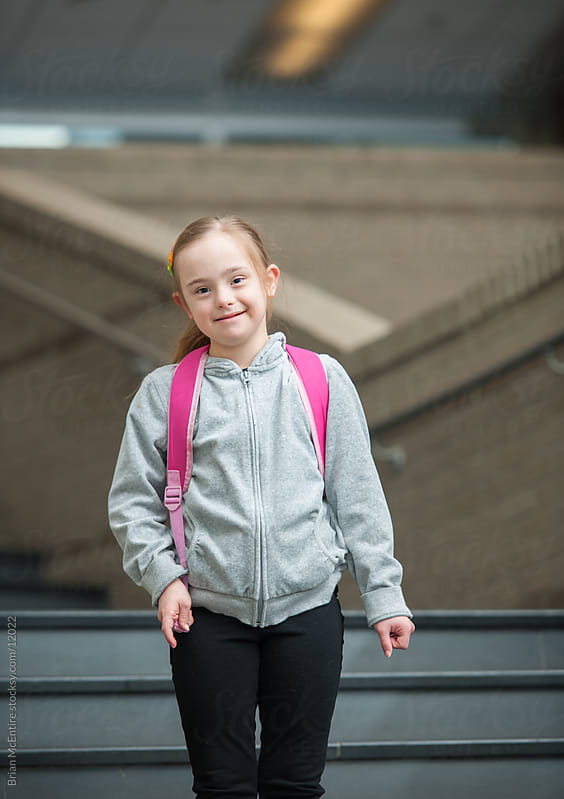Fourth Grade Girl Student with Down Syndrome Wearing Backpack Walking Down Steps by Brian McEntire for Stocksy United