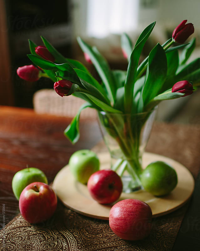 Red tulips in a vase surrounded by red and green apples by kelli kim for Stocksy United