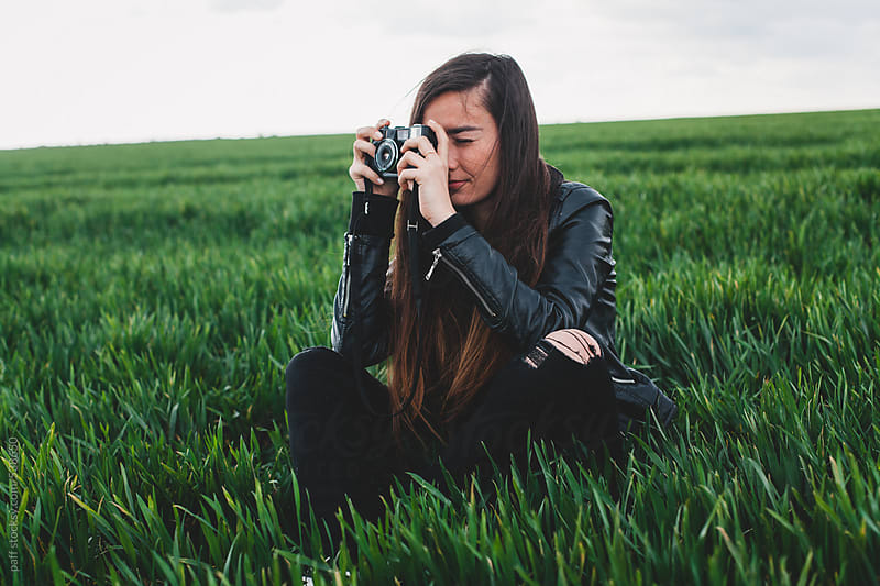 Young woman taking pictures with camera on green grass field by paff for Stocksy United